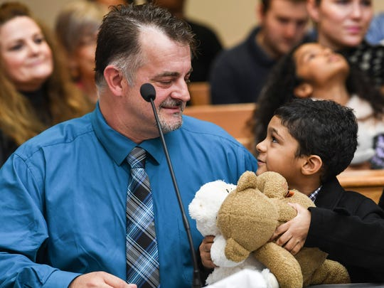 Tim Godfrey of Duncan looks at Aiden Godfrey, his newly adopted son, during a hearing with Judge Edgar Long on State Adoption Day at the Anderson County Courthouse in Anderson on Wednesday.