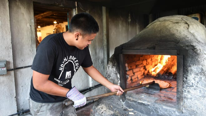 Hotnu Bakery employee Donnie Flores puts a pizza into the oven at Inarajan's Ginen I Tano' Sunday Street Market, August 2015. The festival is scheduled for Sunday Oct. 8, 2017.