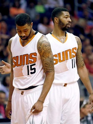 Phoenix Suns' Marcus Morris (15) and his twin brother Markieff Morris (11) take the court during a time out during the second half of an NBA basketball game against the Utah Jazz, Saturday, April 4, 2015, in Phoenix.