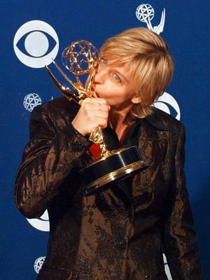 """FILE - In this Sept. 14, 1997 file photo, Ellen DeGeneres kisses her Emmy backstage at the 49th Annual Primetime Emmy Awards in Pasadena, Calif. DeGeneres won the Emmy for outstanding writing in a comedy series for """"Ellen."""" It was 20 years ago that Ellen DeGeneres made history as the first prime-time lead on network TV to come out of the closet. The episode was watched by a staggering 44 million viewers. It won an Emmy for writing, a Peabody as a landmark in broadcasting and numerous other accolades."""