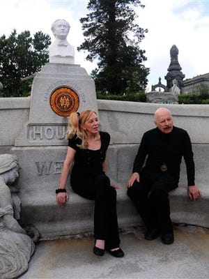 In this 2011 photo provided by Ronald G. Chicken, Dorothy Dietrich and Dick Brookz sit at the grave of legendary magician Harry Houdini at Machpelah Cemetery in the Queens borough of New York. Dietrich and Brookz, magicians and administrators of The Houdini Museum in Scranton, Pa., are working to raise money to restore Houdini's gravesite and permanently care for the monument to him at the cemetery.