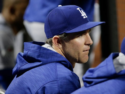 Los Angeles Dodgers' Chase Utley watches play from the dugout during the ninth inning of baseball's Game 3 of the National League Division Series against the New York Mets, Tuesday, Oct. 13, 2015, in New York. The Mets won 13-7. (AP Photo/Julie Jacobson)