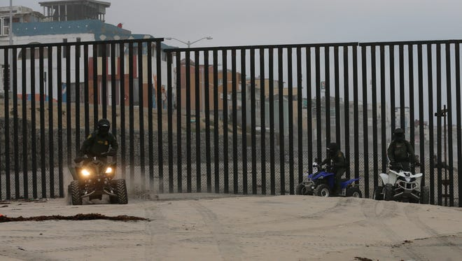 In this June 22, 2016 picture, Border Patrol agents ride all-terrain vehicles along the border structure in front of Playas de Tijuana, Mexico, behind, in San Diego. (AP Photo/Gregory Bull)