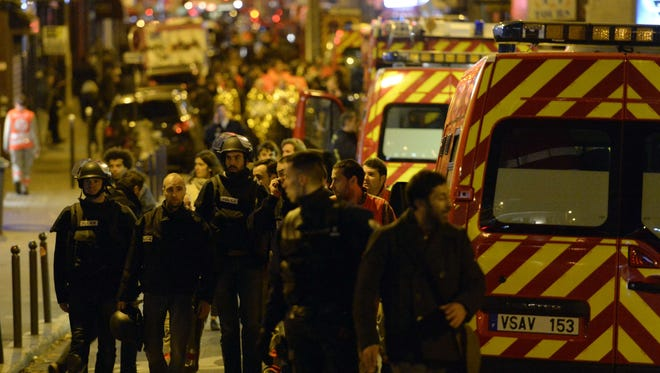Police forces and rescuers walk through rue Oberkampf near the Bataclan concert hall in central Paris, early on November 14, 2015.