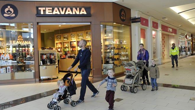 Shoppers walk in front of Teavana when it opened in 2013.