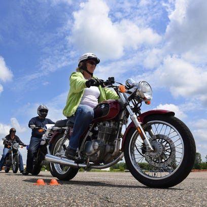 Instructor Tom Travaglio watches while Molly Laudenbach, Kimball, circles the course as she works on her skills before taking the final test for a motorcycle license Sunday at the city of St. Cloud Central Maintenance Facility.