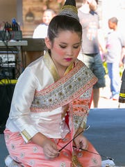 Isabelle Vongrassamy plays a dulcimer at the Boro International Festival  at Cannonsburgh Village in native dress of Wat Amphawan of America. .
