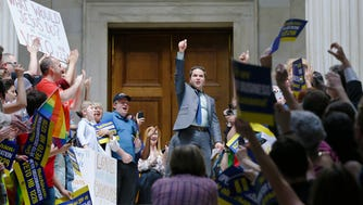 Rep. Warwick Sabin, D-Little Rock, center, cheers with protesters outside of the House chamber at the Arkansas state Capitol in Little Rock, Ark., Monday.