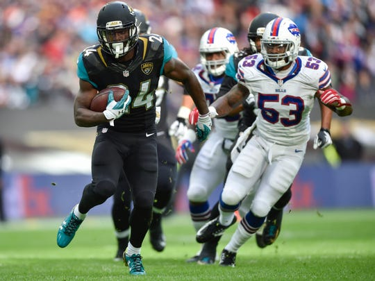 Jacksonville Jaguars running back T.J. Yeldon (24) runs away from Buffalo Bills outside linebacker Nigel Bradham (53) during the first half of the game at Wembley Stadium.