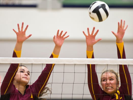 McCutcheon's Alexis Humphrey, left, and Dailey Vanderkolk try to block a shot during their match against Central Catholic Tuesday, August 19, 2014, at CC in Lafayette. McCutcheon won 3-1