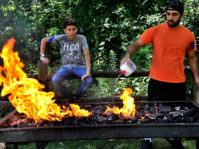 Mohammed Saljabari , right, gets the fire going for the interfaith picnic at Edwin Warner Park on Sunday, June 22, 2014, in Nashville. The picnic was organized by Organized by HELP — Helping Others Promote Excellence.