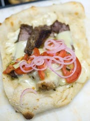 A grilled ribeye flatbread with Swiss cheese, lettuce.