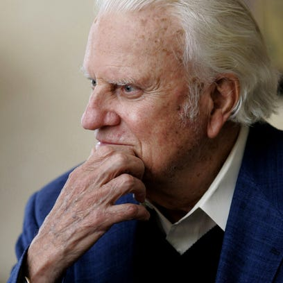 Rev. Billy Graham pauses during an interview in a hotel
