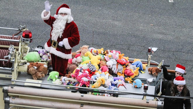 Santa waves with his truck loaded with stuffed animals to give out to children during the parade route at the annual Christmas parade on Main Street in Boonton on November 28, 2015.