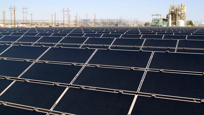 This April 20, 2011 file photo shows dozens of rows of solar panels that make up Public Service Co. of New Mexico's new 2-megawatt photovoltaic array in front of the utility's natural gas-fired generating station in Albuquerque, N.M. The New Mexico Attorney General's office and consumer advocates on Wednesday, Aug. 30, 2017, presented a petition to state regulators to consider adopting a clean energy standard that calls for utilities to reduce their carbon dioxide emissions.