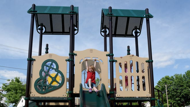Siblings Lela and E.J. play together on the new playground equipment at Bancroft Park in Coshocton. The park had new equipment and a walking path installed.