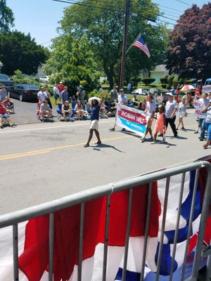 """Robin Wilt, a 136th Assembly District candidate, marches in the Irondequoit Fourth of July parade with supporters holding  """"Robin Wilt for Assembly"""" signs."""