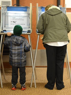 Candace Krist votes whike her son, Joe, checks out a voting booth at the Allouez Village Hall in 2014. Candidates for Brown County elections next year have until Jan. 5 to file the necessary paperwork.