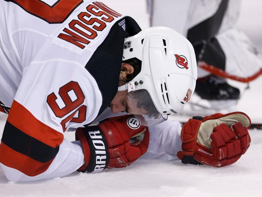 New Jersey Devils left wind Marcus Johansson (90) reacts after an injury during the third period against the Boston Bruins at TD Garden.