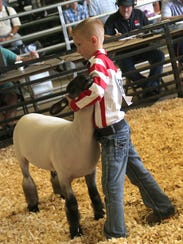 Peyton McMahan shows his Grand Champion lamb during