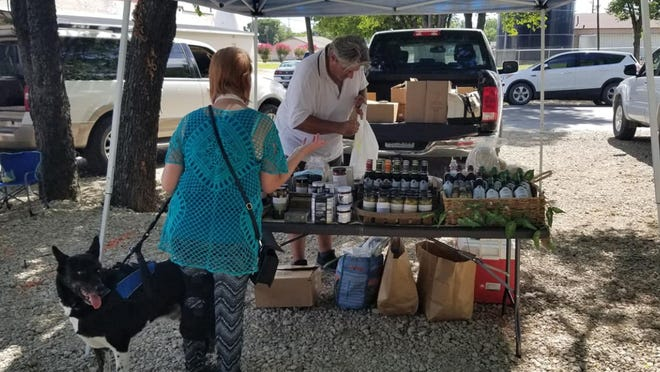 A vendor at the Railcar Farmers Market of Van Alstyne, right, assists a customer with a purchase. The market is scheduled from 4-7 p.m. Tuesdays, through Oct. 13.