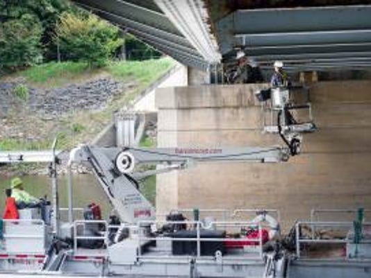 Jordan Good, left, uses a hammer to determine the integrity of steel under corrosion, while Logan Swartz, right, documents each area of the bridge the C.S. Davidson Inc. crew investigates. The Princess Street bridge over the Codorus Creek in York was inspected Wednesday October 10, 2012 using an 8 ton bucket boat from Harcon Corporation, of Paradise.  ( YORK DAILY RECORD/SUNDAY NEWS - PAUL KUEHNEL)