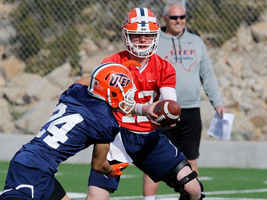 UTEP senior quarterback Ryan Metz hands the ball of