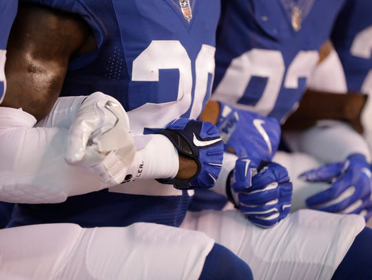 Members of the Indianapolis Colts lock arms as they