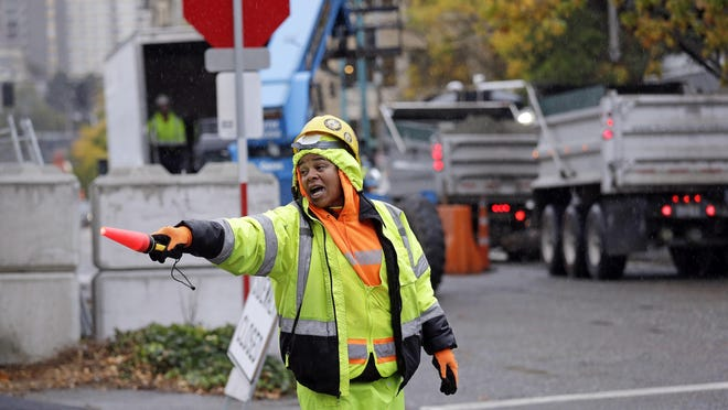 Andrea Benard directs traffic at an Amazon construction in Seattle. In the decade since the recession began, coastal cities have opened an income gap on their counterparts in between.