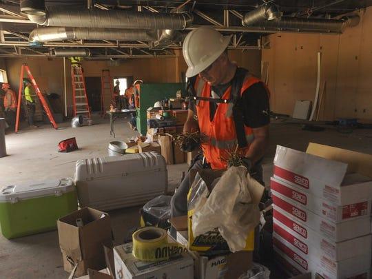 ROB VARELA/THE STAR Carpenter Emanuel Rivera grabs two handfuls of nails as he works in what will be the training room at the Rams practice facilities on the campus of CLU in Thousand Oaks.