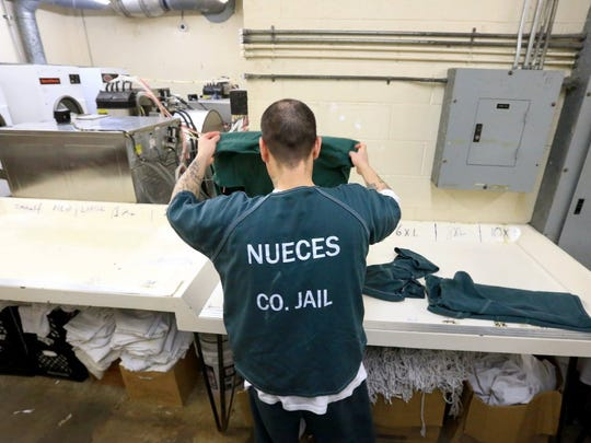 An inmate folds clothes in the laundry room at the