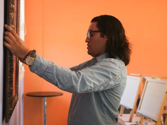 Alejandro Castanon hangs a painting at Vino Dipinte Art Gallery, 602 Orient St.