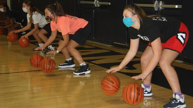"""From left, Ashya Bates, Addie Switzer, Mariah Reading and McKinley Rexroat are doing the type of """"double dribble"""" that's allowed in basketball, working on their ball handling during a Monmouth-Roseville contact day Monday, Oct. 5."""