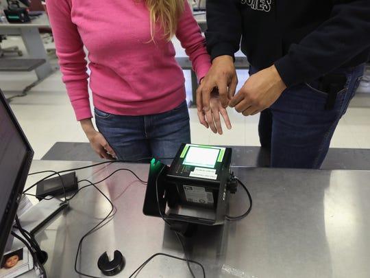 Un agente de inmigración le toma las huellas a una joven.