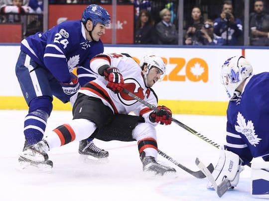 Devils center Adam Henrique (14) draws a penalty as