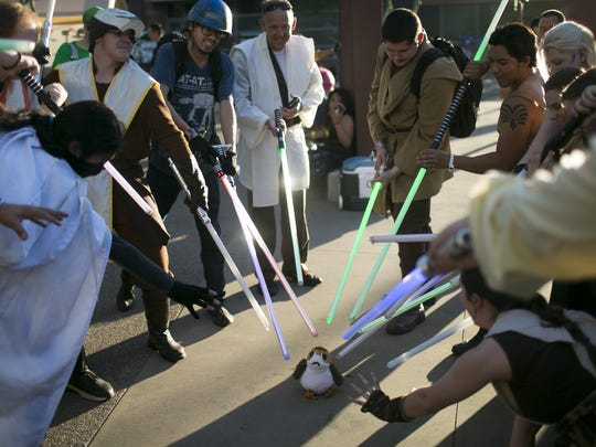 Cosplayers point their lightsabers at a stuffed animal