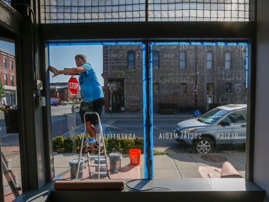 Mason Bybee puts painters tape around a window on Commercial