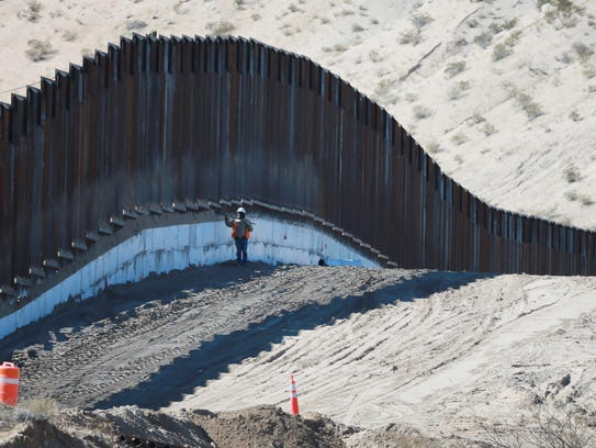 A construction worker clears dirt from the new border