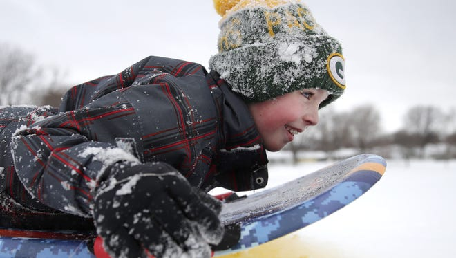 Jackson Custer, 8, of Neenah, begins his decent down a sledding hill Monday at Quarry Park in Neenah.