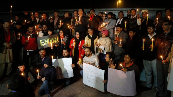 Pakistani civil society members take part in a candlelight vigil for the victims of a Taliban attack at a school in Peshawar on Dec. 16, 2014, in Islamabad, Pakistan.
