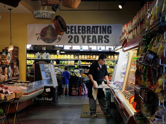 A 20-year anniversary sign hangs at Tuscany Specialty