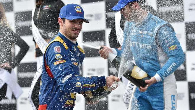 Alexander Rossi sprays the champagne on third-place finisher Ed Jones in Victory Circle after winning the Toyota Grand Prix of Long Beach -- Photo by: Chris Owens