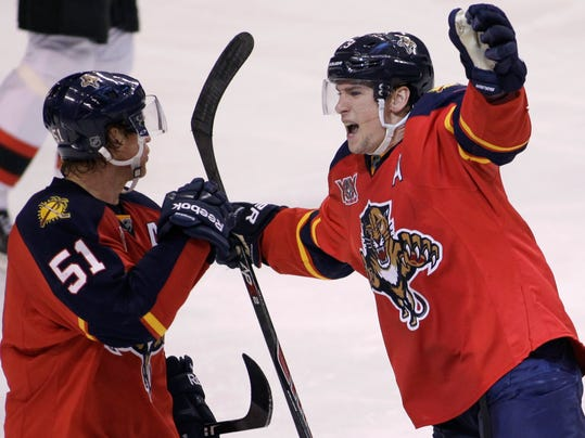 Florida Panthers' Scottie Upshall, right, celebrates with teammate Brian Campbell (51) after Upshall scored a goal during the third period of an NHL hockey game against the New Jersey Devils, Friday, March 14, 2014, in Sunrise, Fla. The Panthers won 5-3. (AP Photo/Luis M. Alvarez)