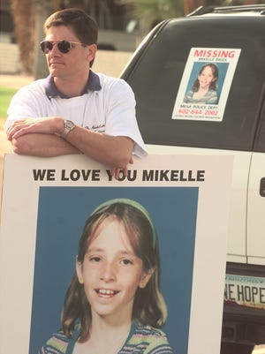 Darien Biggs holds a sign with a photo of his missing daughter, Mikelle Biggs, in 1999.