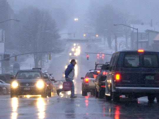 File photo from a previous winter shows a pedestrian dashing across Main Street in Burlington as a mixture of sleet and snow falls late in the afternoon.