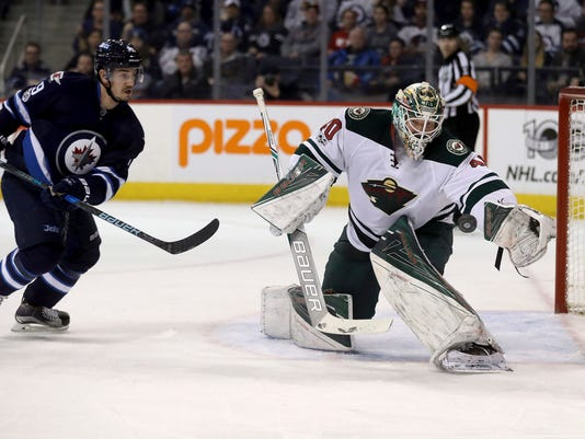 Minnesota Wild goalie Devan Dubnyk (40) looks to make a glove save in front of Winnipeg Jets left wing Nic Petan (19) during the second period of an NHL hockey game Tuesday, Feb. 7, 2017, in Winnipeg, Manitoba. (Trevor Hagan/The Canadian Press via AP)