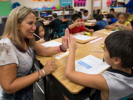 Lehi Elementary principal Darlene Johnson works with second grade student Izayah Mendez during the first day of school in Mesa August 6, 2014.