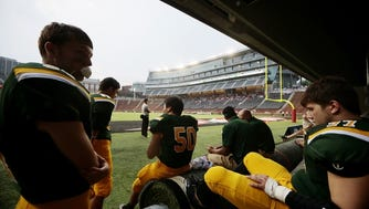 Sycamore players wait during a lightning delay of their game against La Salle at Nippert Stadium.