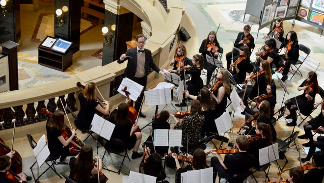 Wauwatosa East orchestra teacher/director Mike Hayden conducts the orchestra at the state capitol building.