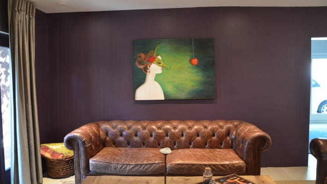 A piece of Roza Fedowsmakan's original work hangs over a rustic leather couch in the home's living room, which is enclosed with an eggplant-colored wall.